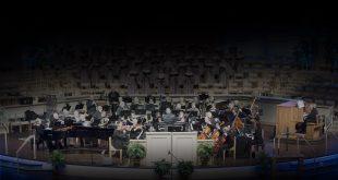 uma orquestra reunida e se apersentando com um coral ao fundo