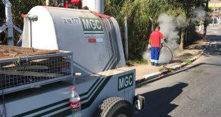 caminhonete com o herbicida ecológico e um homem aplicando-o ao fundo
