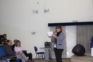 professora fala ao microfone durante palestra