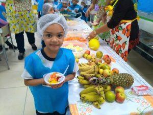 aluna posa para foto com pratinho cheio de frutas ao lado de mesa com várias frutas