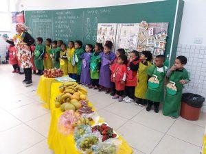 alunos e professores alinhados na parede atrás de uma mesa cheia de frutas