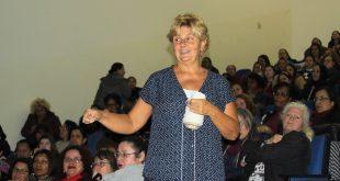 Leigh Ann Kramer proferindo sua palestra com várias educadoras lotando auditório ao fundo