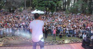 projota fotografado de costas com grande público visível ao fundo