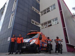 dois agentes da  defesa civil de barueri posam em suas motos ao lado de uma van do órgão com duas outras agentes posando ao lado