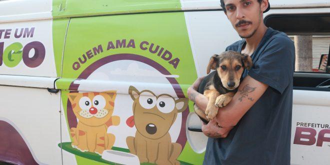 um morador de baruri segura um cãozinho em seu colo enquanto olha para a câmera diante de uma vã do programa adote um amigo