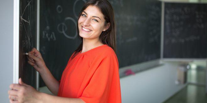 uma estudante universiaária sorri para a câmera enquanto escreve na lousa