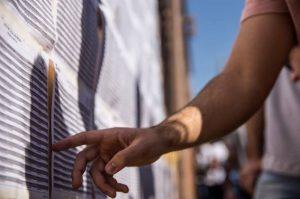 detalhe da mão de um candidato conferindo listas de aprovados