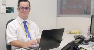 portador de síndrome de down sorridno para a câmera enquanto trabalha em um notebook