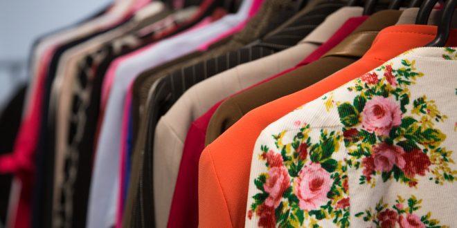 várias roupas com cores e estampas diferentes penduradas num cabideiro