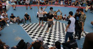 dançarinos dançam break num palco xadrez preto e branco, enquanto o público acompanha em arquibancadas circundando o tablado