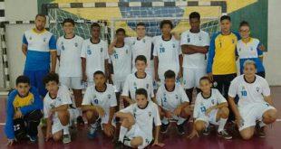 equipe infantil de handebol posando para foto diante do gol