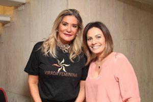 duas mulheres sorrindo para a camera, uma delas usando uma camiseta da Virada Feminina