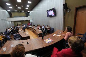 mulheres em mesa de discussão falando para público misto