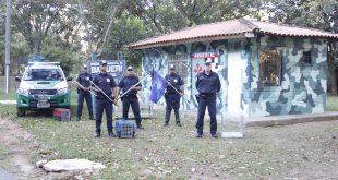 cinco homens da Guarda Ambiental de Barueri posam com armas diante do posto da corporação, com uma viatura atrás e à direita deles