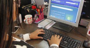 uma mulher acessa o site do Procon por meio de um notebook
