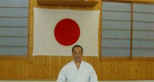 Ruy Koike ajoelhado de kimono branco diante de uma bandeira do Japão estendida na parede
