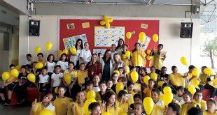 alunos e professores de escola municipal de Barueri segurando balões amarelos em campanha contra a febre amarela