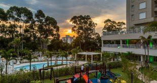 perspectiva artística de um predio de luxo, com piscina e playground no primeiro plano