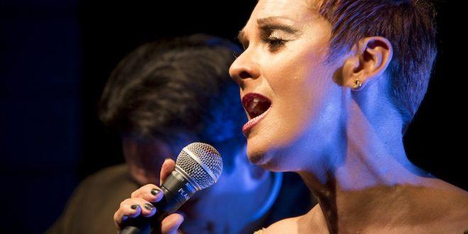 um close do rosto da cantora Mafalda Minnozzi cantando ao microfone, com o rosto voltado para a esquerda da imagem
