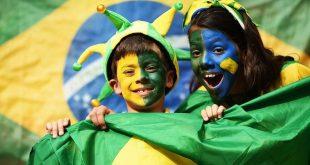 crianças com os rostos pintados para torcer pelo Brasil, com uma bandeira brasileira ao fundo