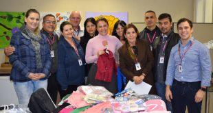 membros do fundo social de solidariedade posam para foto diante de peças doadas durante a campanha do agasalho