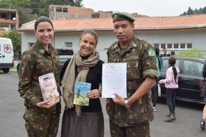 soldados do exército e mulher posam para foto durante ação em Baruei