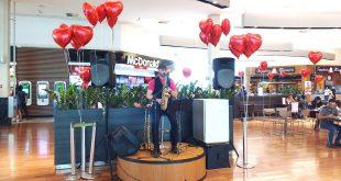 um músico se apresentando no palco da praça de alimentação do Parque Shopping Barueri com balões de corações dispostos em volta durante o Barueri Music especial de Dia dos Namorados