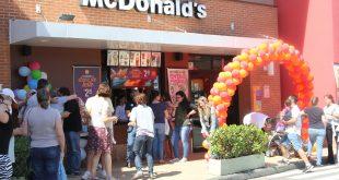 pessoas reunidas em frente a uma unidade do McDonald's durante o McDia Feliz