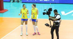 duas jogadoras da seleção brasileira de vôlei sendo filmadas na quadra por um cinegrafista