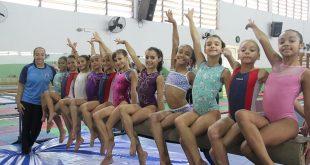 uma turma de ginastas artísticas de Barueri sorri e faz pose para a câmera, acompanhadapor uma treinadora