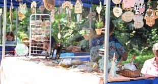 um estande da feira de artes, decoração e artesanato, com diversos objetos de artesanato pendurados e dispostos