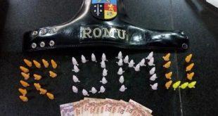 entorpecentes dispostos numa mesa de modo a formar a palavra 'ROMU'; há também cédulas de real