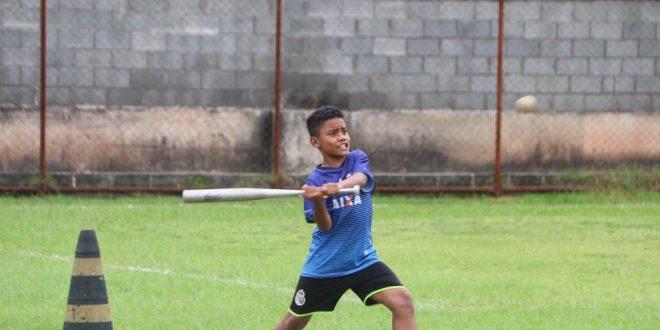 aluno do Barueri Esporte Forte prestes a atingir uma bola de beisebol com seu taco