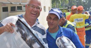 dois homens sorriem para a câmera com kits recebidos pela campanha do agasalho