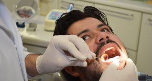 um caminhoneiro tendo sua boca examinada pelas mãos de um(a) dentista(a)