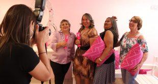fotógrafa registra imagem de quarteto de mulheres segurando almofadas rosas