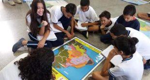 alunos sentados em volta de um mapa na Emef Lenio
