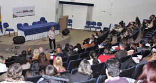 professores reunidos em auditório para acompanhar palestra da educadora Tatiana Pita, vista no palco
