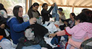 cidadças vasculham pilha de roupas para selecionar peças