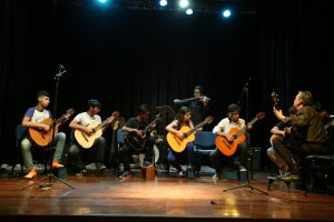 um grupo de alunos se apresentando ao violão