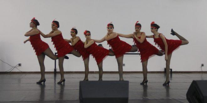 sete mulheres alinhadas e apoiadas umas nas outras e com os pés direitos no chão e os esquerdos levantados até a altura da cintura