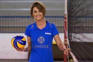Kasia Skowronska posa ao lado da rede com uma bola na mão direita enquanto sorri para a câmera vestida com o uniforme do Hinode Barueri