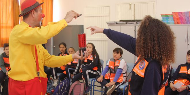 palhaço fala com turma de agentes mirins auxiliado por uma das alunas