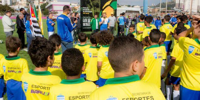 pequenos atletas observam equipe do cbf social discursando