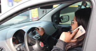 uma motorista fala ao celular enquanto conduz seu carro