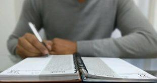 uma pessoa escrevendo em uma agenda,; sua cabeça não é mostrada