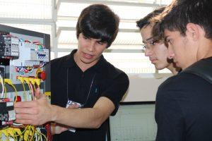 estudante explica instalação tecnológica para dois visitantes durante ExpoTec