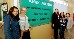 representantes posam ao lado de mural da escola com professoras