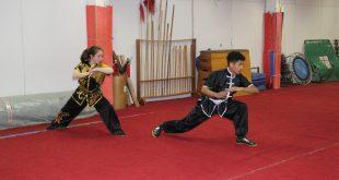 dois atletas de kung fu praticam movimentos