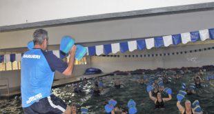 mulheres se exercitando em piscina sob orientação de um profissional